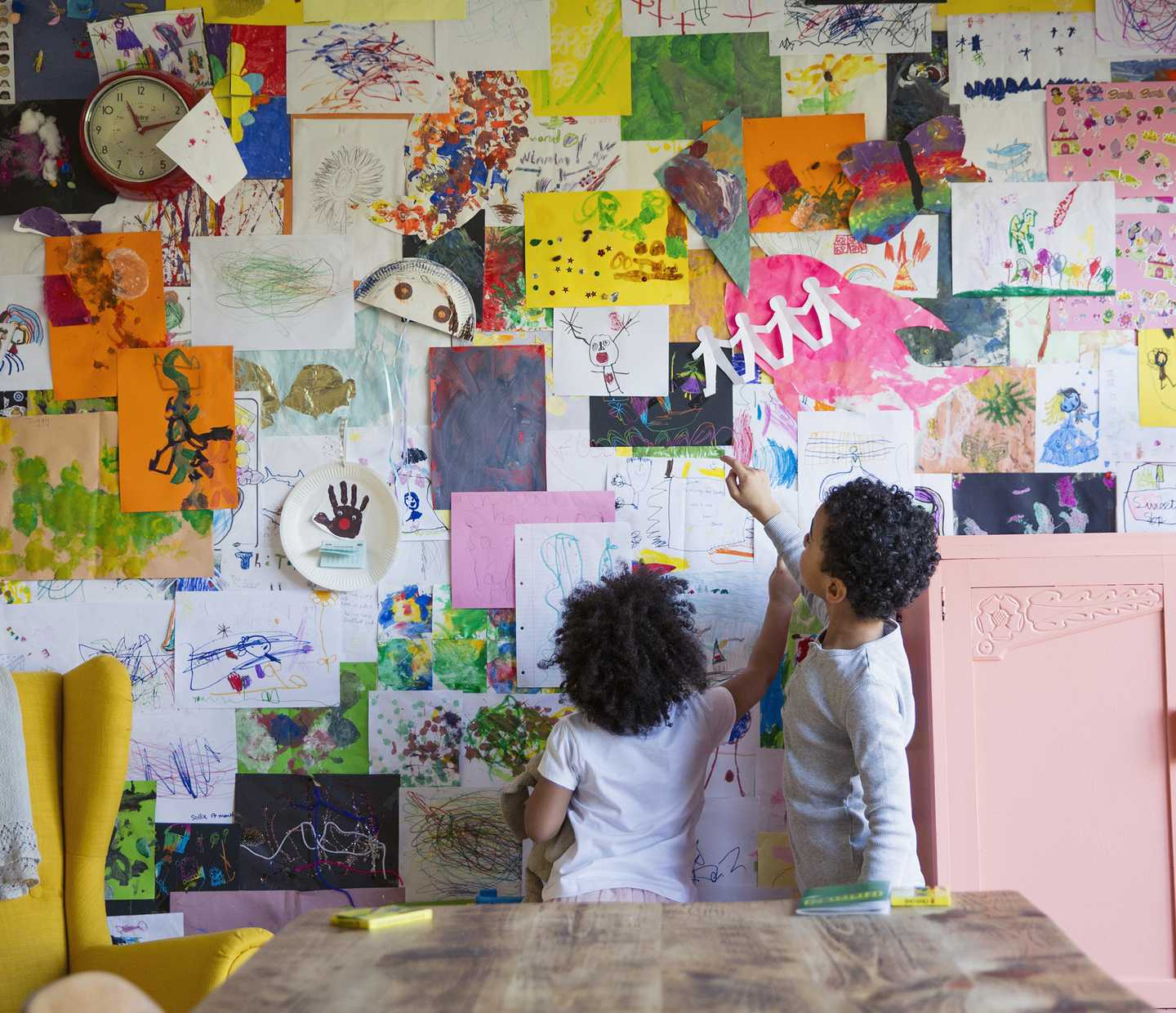 Two young children at a wall of handmade art