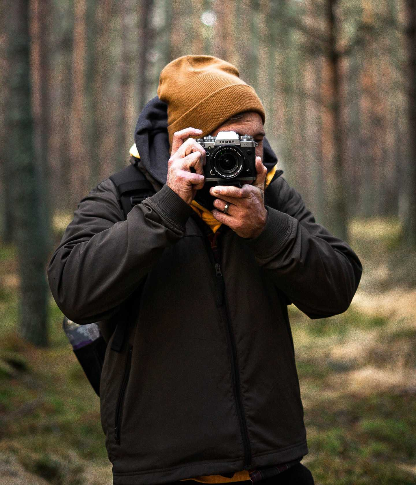 Man in woods shooting a photo