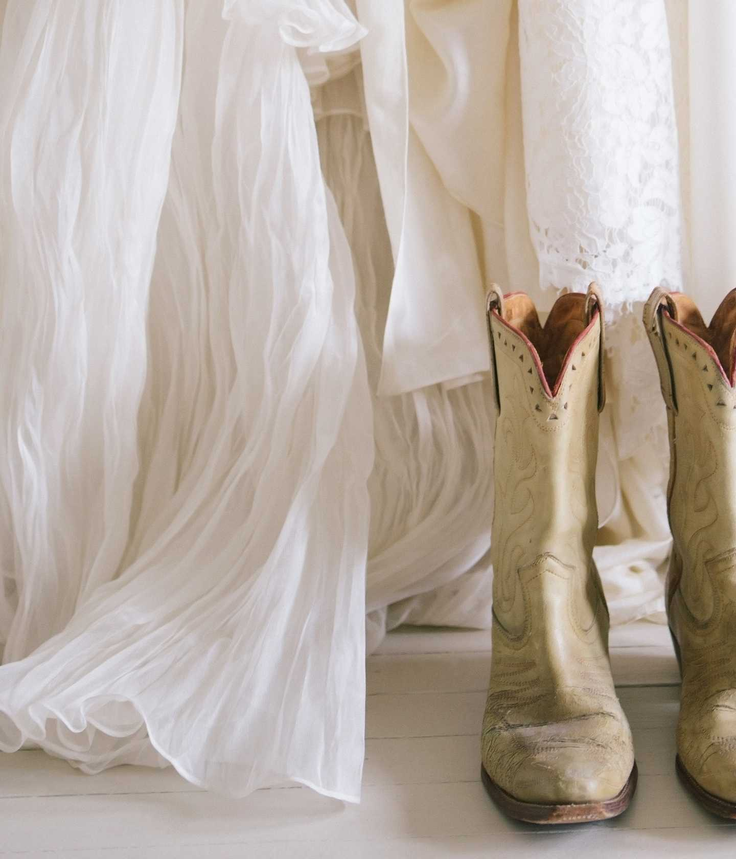 The hems of several white dresses and a pair of cowboy boots