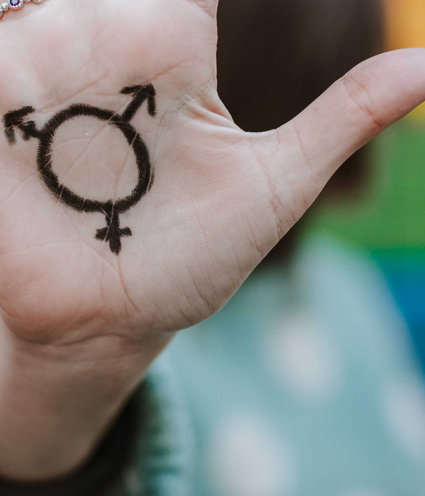 Hand with drawing of different gender signs on palm