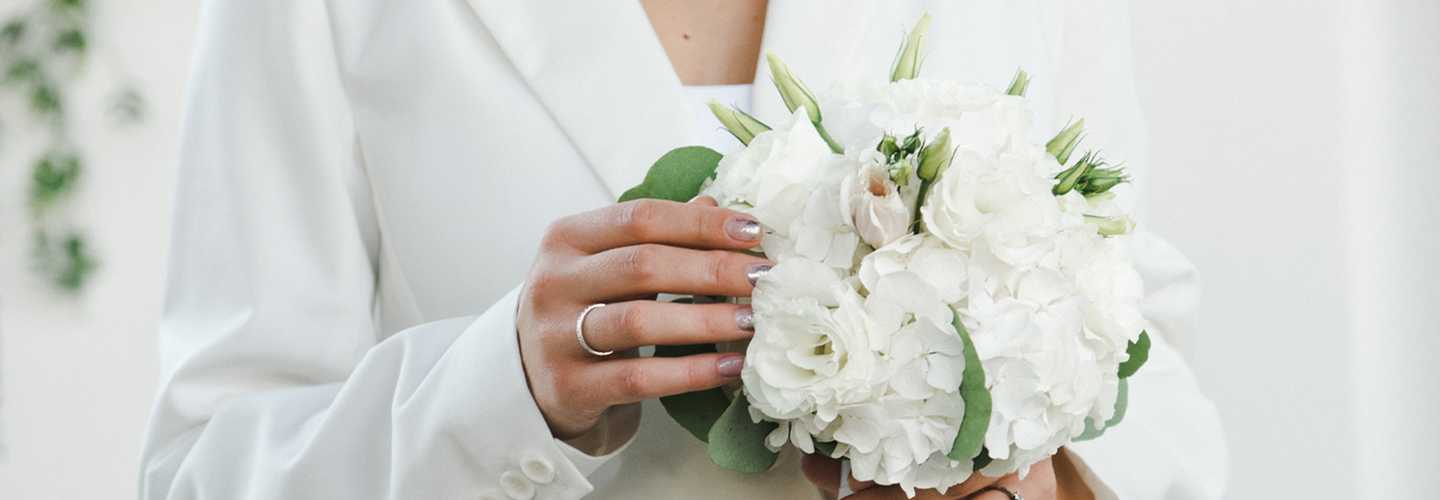 Torso of person wearing white suit holding wedding bouquet
