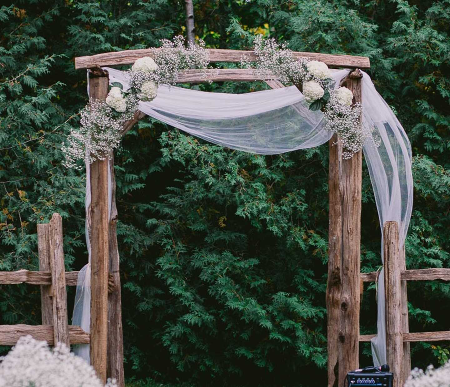 Weathered arbour draped with flowers and fabric